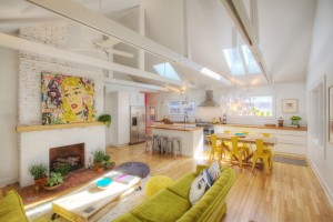 Broad Ripple Bungalow - Green Retro Sofas, Pallet Coffee Table on Wheels Poufs Exposed Structure Trusses Painted Brick - HAUS Architecture, WERK Building Modern, Christopher Short, Indianapolis Architect