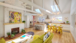 Broad Ripple Bungalow Renovation, Green Retro Sofas Kitchen Island Yellow Metal Chairs Reclaimed Dining Table Large Pop Art Poufs Painted Brick Exposed Truss Beams Vaulted Ceilings, HAUS Architecture, Christopher Short, Indianapolis Architect