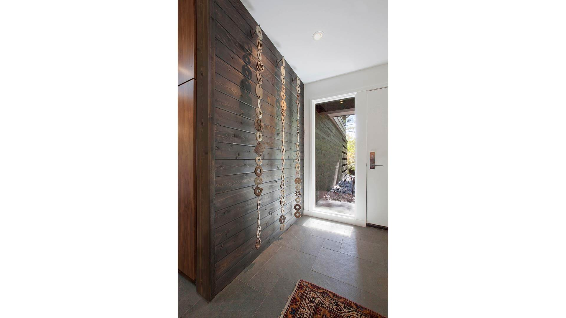 Mid Mod Entry Wall, Foyer. red entry door, entry skylight, track lighting, Ceramic Art, grey slate entry floor tile, custom artwork, Walnut Cabinetry, red area rug, inside-out entry wall - Midcentury Modern Renovation - 81st Street - Indianapolis, Christopher Short, Architect, HAUS Architecture