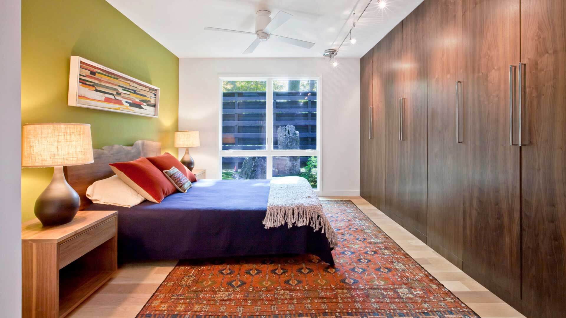 Master Bedroom, large red area rug, Walnut cabinet wall, large window to private moss garden court, custom artwork, track lighting, white modern ceiling fan, blue bedspread, wide plank white oak flooring - Midcentury Modern Renovation - 81st Street - Indianapolis, Christopher Short, Architect, HAUS Architecture
