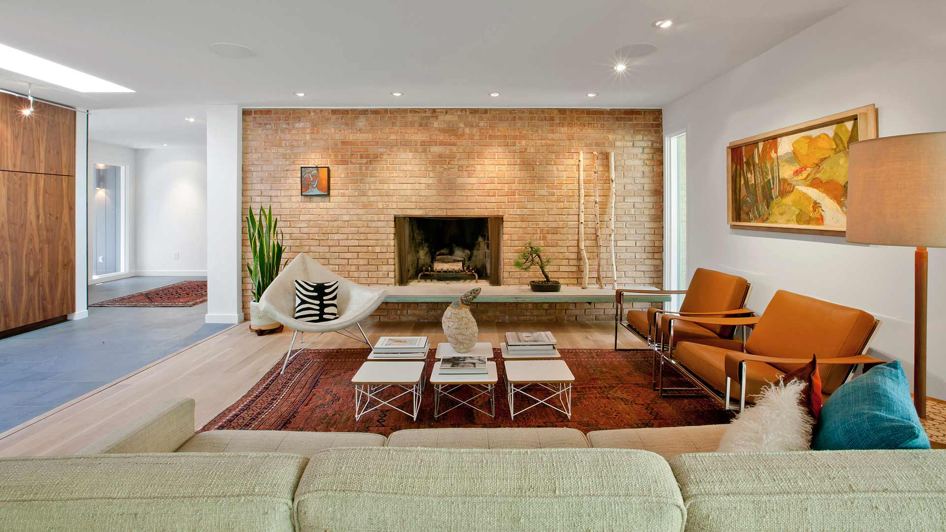 Original Mid Mod Fireplace, raised concrete hearth, modern furniture, large red area rugs, custom artwork, retro furnishings, inside out brick wall, exposed brick, leather side chairs, linen sofa, flokate pillow, wide plank oak flooring - Midcentury Modern Renovation - 81st Street - Indianapolis, Christopher Short, Architect, HAUS Architecture