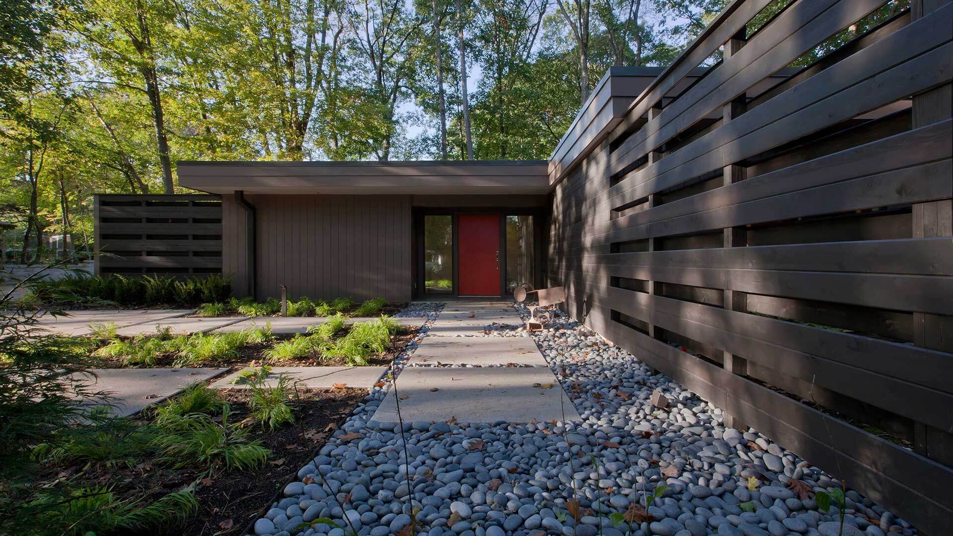 Red door, Mid Mod Entry, screenwall, dog run, modern landscaping, river stone, river rock, steel site sculpture, concrete pavers, concrete pads, steel sculpture, flat roofs, roof overhangs - Midcentury Modern Renovation - 81st Street - Indianapolis, Christopher Short, Architect, HAUS Architecture