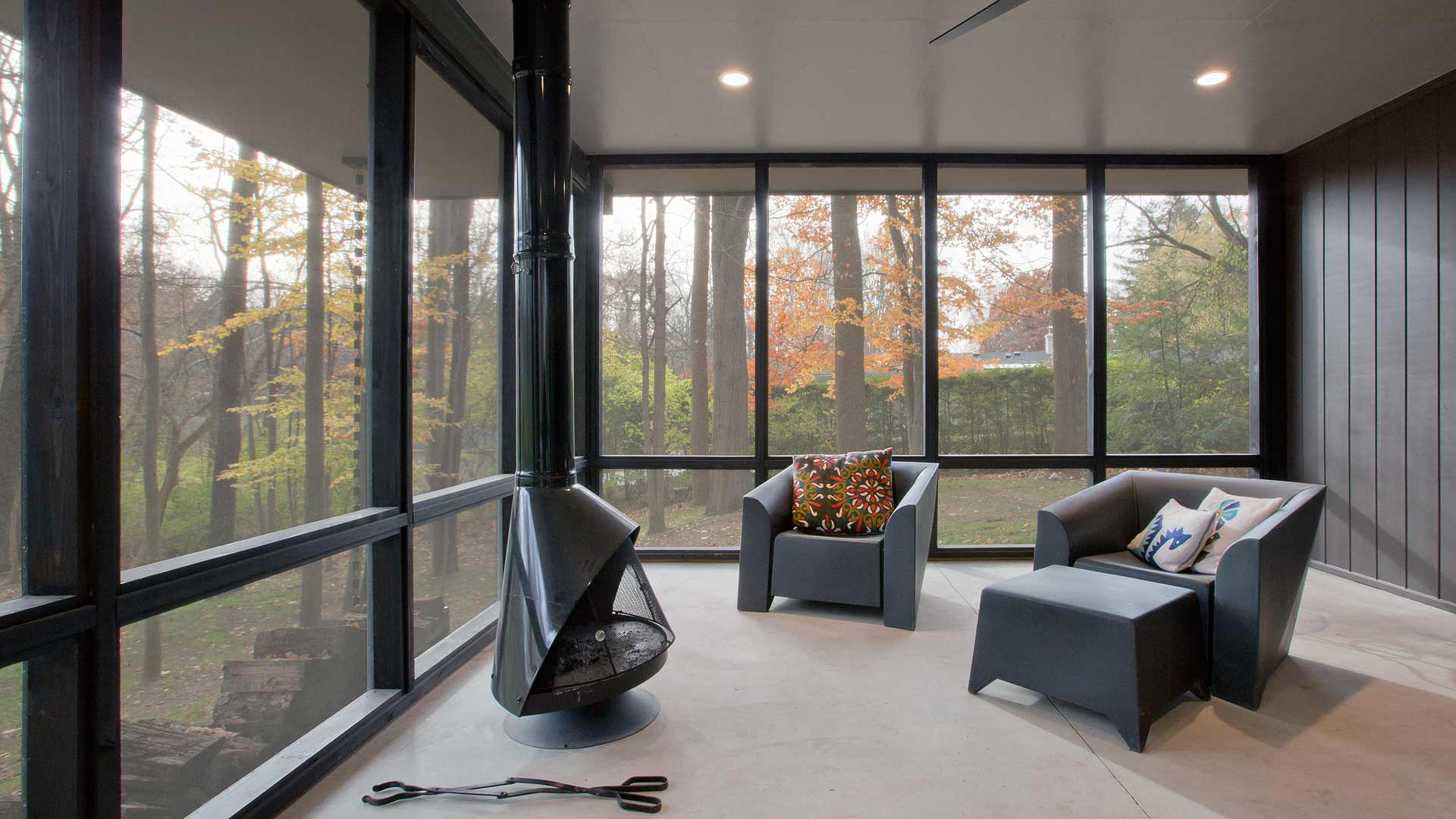 Mid Mod Screened Porch, retro steel fireplace, modern fireplace, porch fireplace, black steel fireplace, porch furniture, wooded site views, porch ceiling fan - Midcentury Modern Renovation - 81st Street - Indianapolis, Christopher Short, Architect, HAUS Architecture