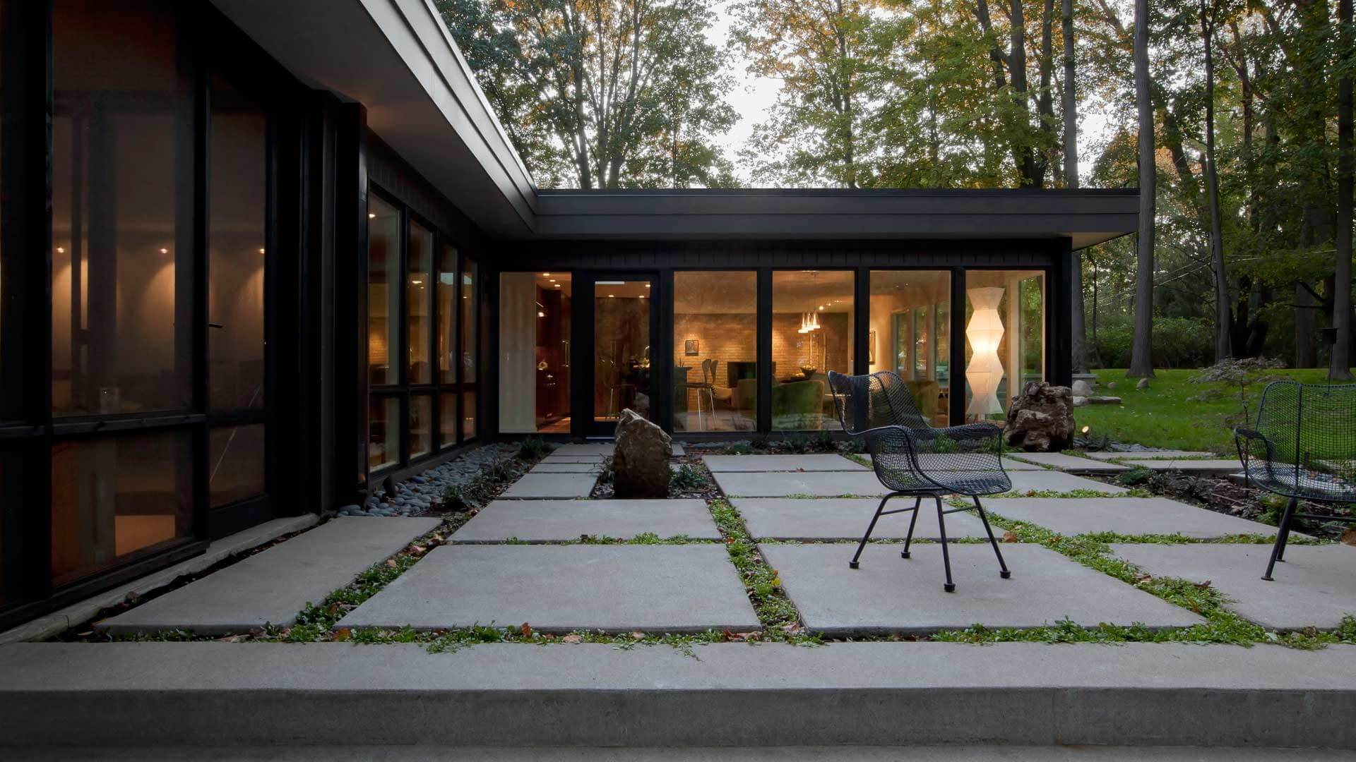 Dezeen Magazine Features HAUS Project - Flat Roofs, large windows, giant windows, window walls, private moss garden, private terrace, wooded site, concrete pavers, concrete pads, modern landscaping, screened porch, floor to ceiling windows, paper lanterns, Noguchi floor lamp, brick fireplace - Midcentury Modern Renovation - 81st Street - Indianapolis, Christopher Short, Architect, HAUS Architecture