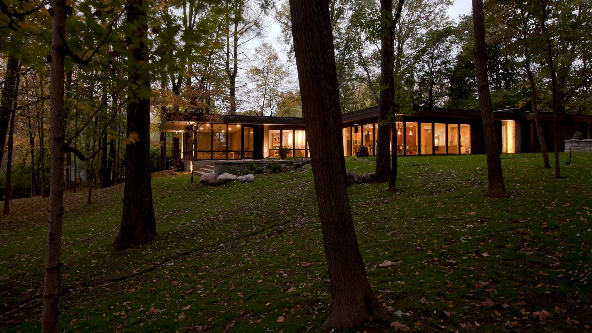 Flat Roofs, large windows, giant windows, window walls, private terrace, wooded site, concrete pavers, concrete pads, modern landscaping, screened porch, floor to ceiling windows, brick fireplace, sloping site, twilight photography, architectural photography - Midcentury Modern Renovation - 81st Street - Indianapolis, Christopher Short, Architect, HAUS Architecture