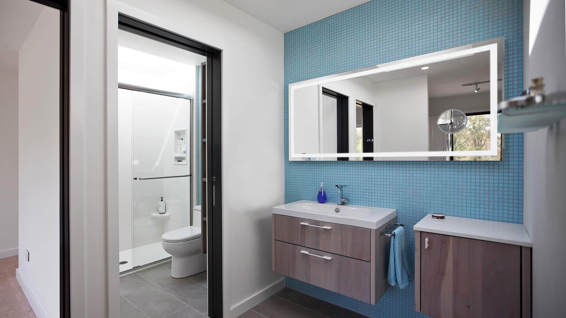 Kid Bathroom with Skylights, blue mosaic tile, lighted mirror, custom wall-hung vanity, shower skylight, vanity skylight, porcelain tile floor - New Modern House 1 - Zionsville, Indiana, Christopher Short, Architect, HAUS Architecture