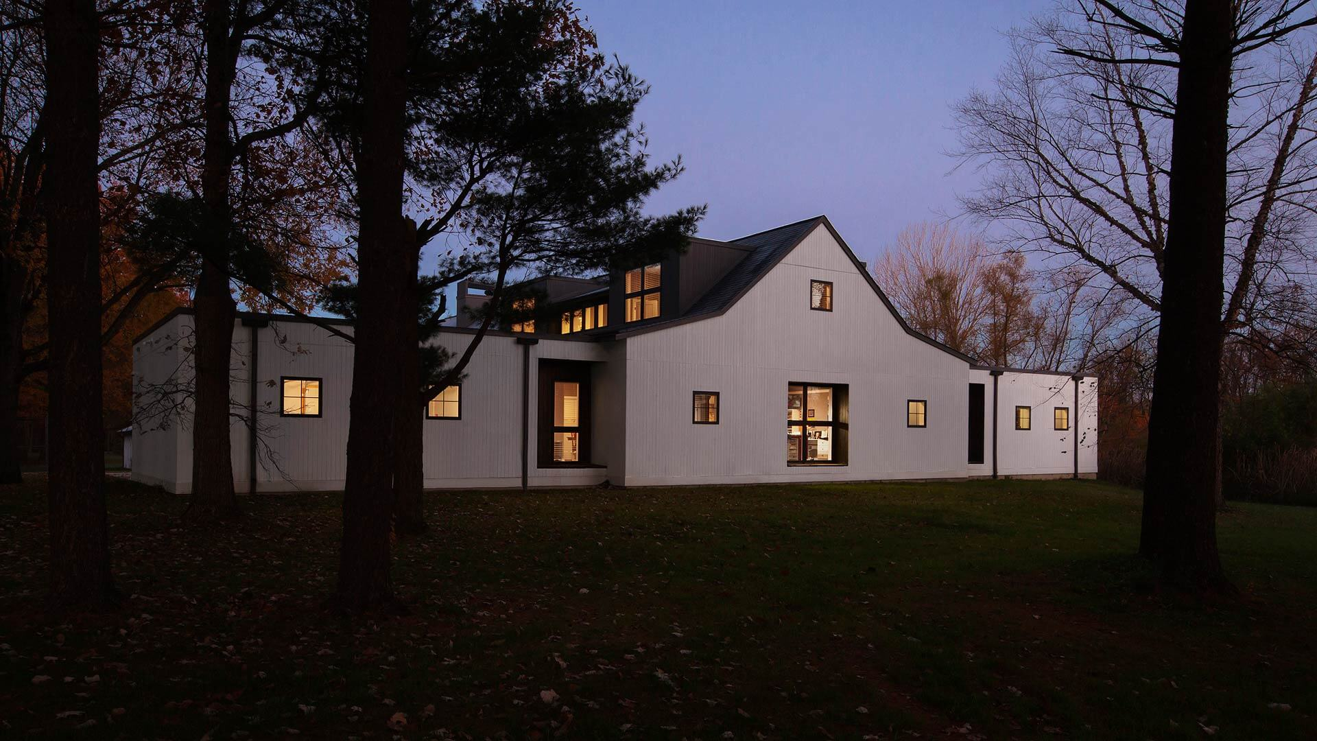 white siding, dawn, dormers, flat roofs, forest trees, fall, downspouts, black windows, large windows, giant windows, vertical siding, Exterior Elevation - Modern Farmhouse 2 - Zionsville - Indianapolis - HAUS Architecture For Modern Lifestyles, Christopher Short, Architect, AIA, NCARB, LEED AP BD&C