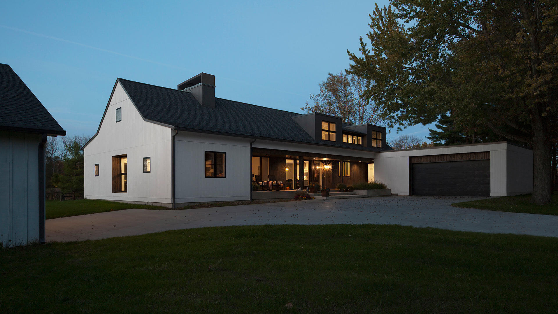 front porch, Halloween, deep inset windows, smooth garage door, black garage door, porch lighting, white siding, dawn, dormers, flat roofs, forest trees, fall, downspouts, black windows, large windows, giant windows, vertical siding, Exterior Elevation - Modern Farmhouse 2 - Zionsville - Indianapolis - HAUS Architecture For Modern Lifestyles, Christopher Short, Architect, AIA, NCARB, LEED AP BD&C