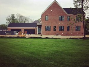 Brick installation is nearing completion and awaits painted finish (west elevation) - Modern Colonial House - Towne Oak Estates, Steffe Drive, Carmel, Indiana - Christopher Short, Derek Mills, Paul Reynolds, Indianapolis Architects, HAUS | Architecture For Modern Lifestyles