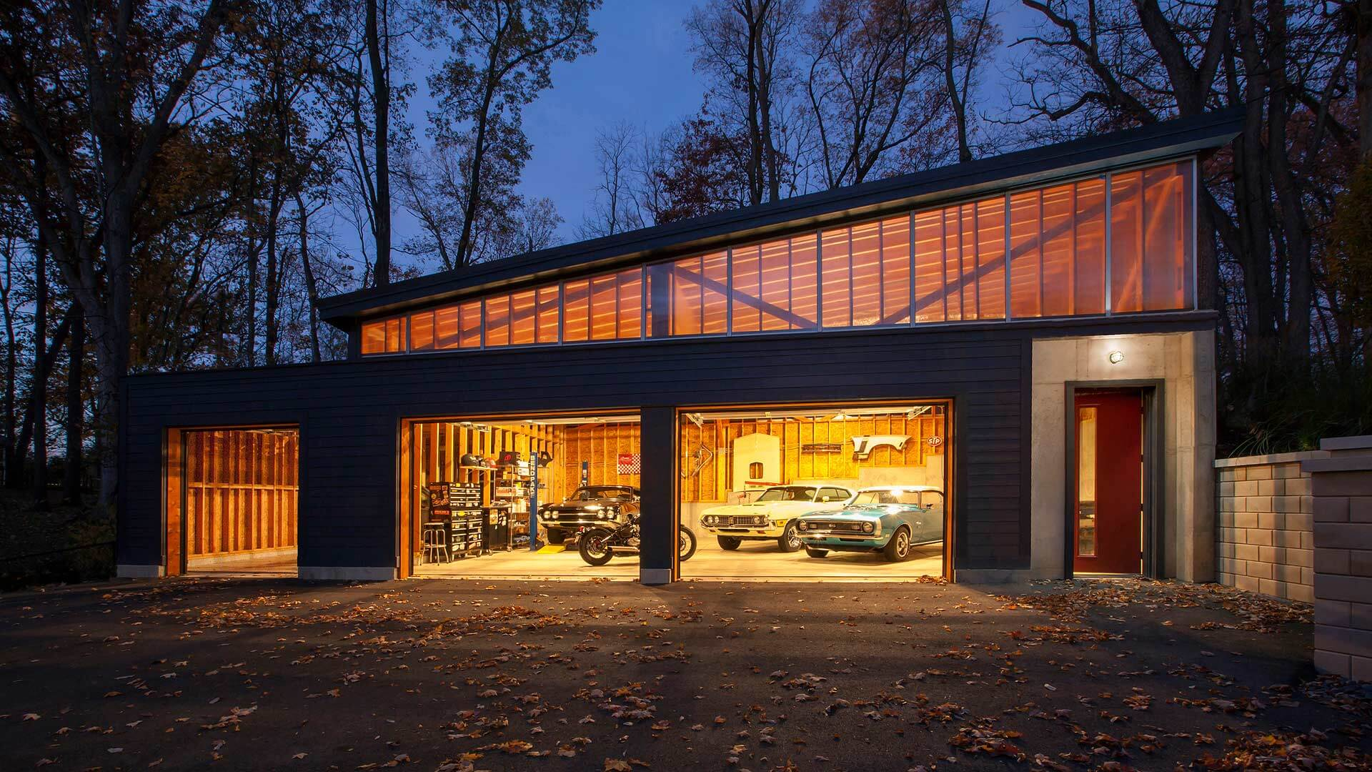 Front view of of auto garage workshop at dawn features raised clerestory shed roof that compliments the lines of pre-existing house - Vintage Modern Garage - 1950's Midcentury Modern Renovation & Detached Workshop Addition, Traders Point Lake - Lakeside, 7150 Lakeside Drive, Indianapolis, Indiana - Christopher Short, Paul Reynolds, Indianapolis Architects, HAUS | Architecture For Modern Lifestyles