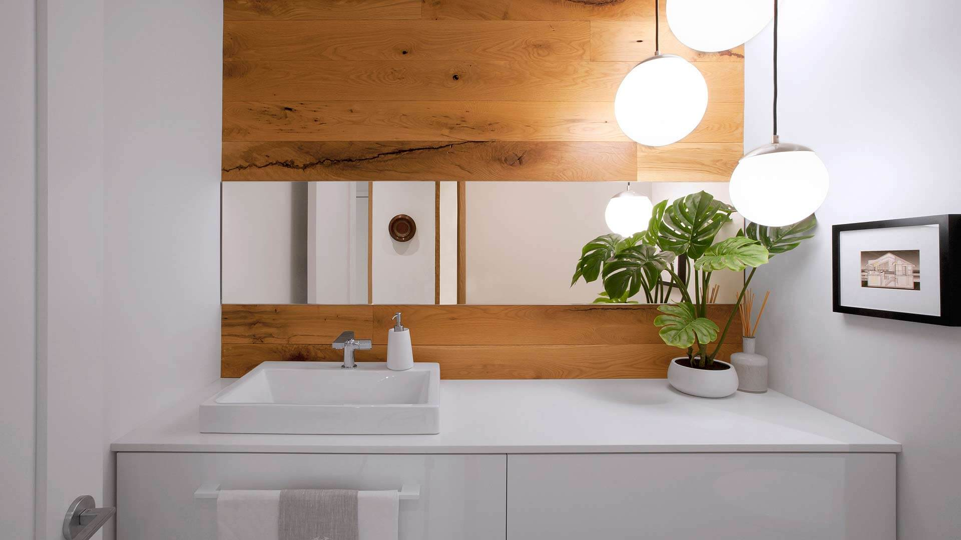 New powder room incorporates white oak into vanity wall with floating white vanity, horizontal mirror, and ball pendant lighting - Modern Lakehouse Renovation - Clearwater - HAUS | Architecture For Modern Lifestyles - Christopher Short, Architect - Derek Mills, Project manager - WERK | Building Modern (Construction Manager + Custom Builder)