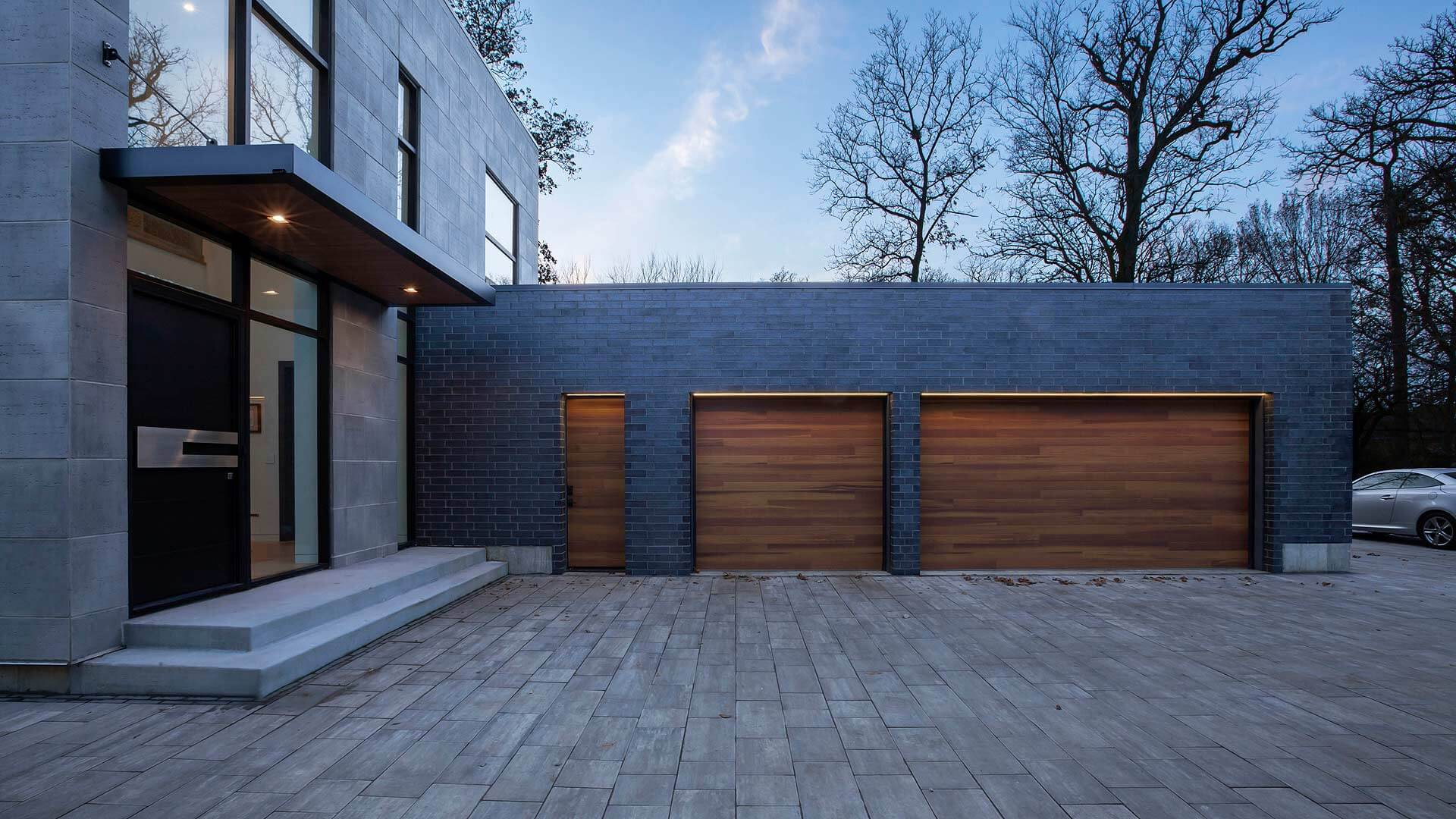 3-Car Garage features horizontal wood door slats (faux), dark gray brick, and buff pavers, and black-frame modern window frames - Minimalist Modern - Indian Head Park - Chicago, Illinois - HAUS | Architecture For Modern Lifestyles, Christopher Short, Indianapolis Architect with Joe Trojanowski