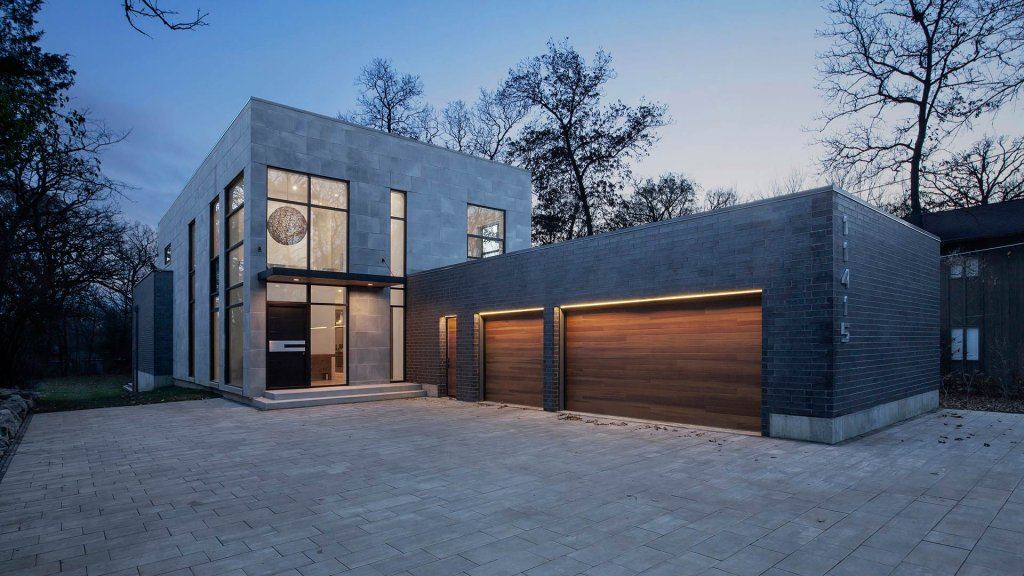 Front Elevation at dusk highlights the brick/concrete paver facade, Fleetwood Windows, and minimal modern design - Minimalist Modern - Indian Head Park - Chicago, Illinois - HAUS | Architecture For Modern Lifestyles, Christopher Short, Indianapolis Architect with Joe Trojanowski