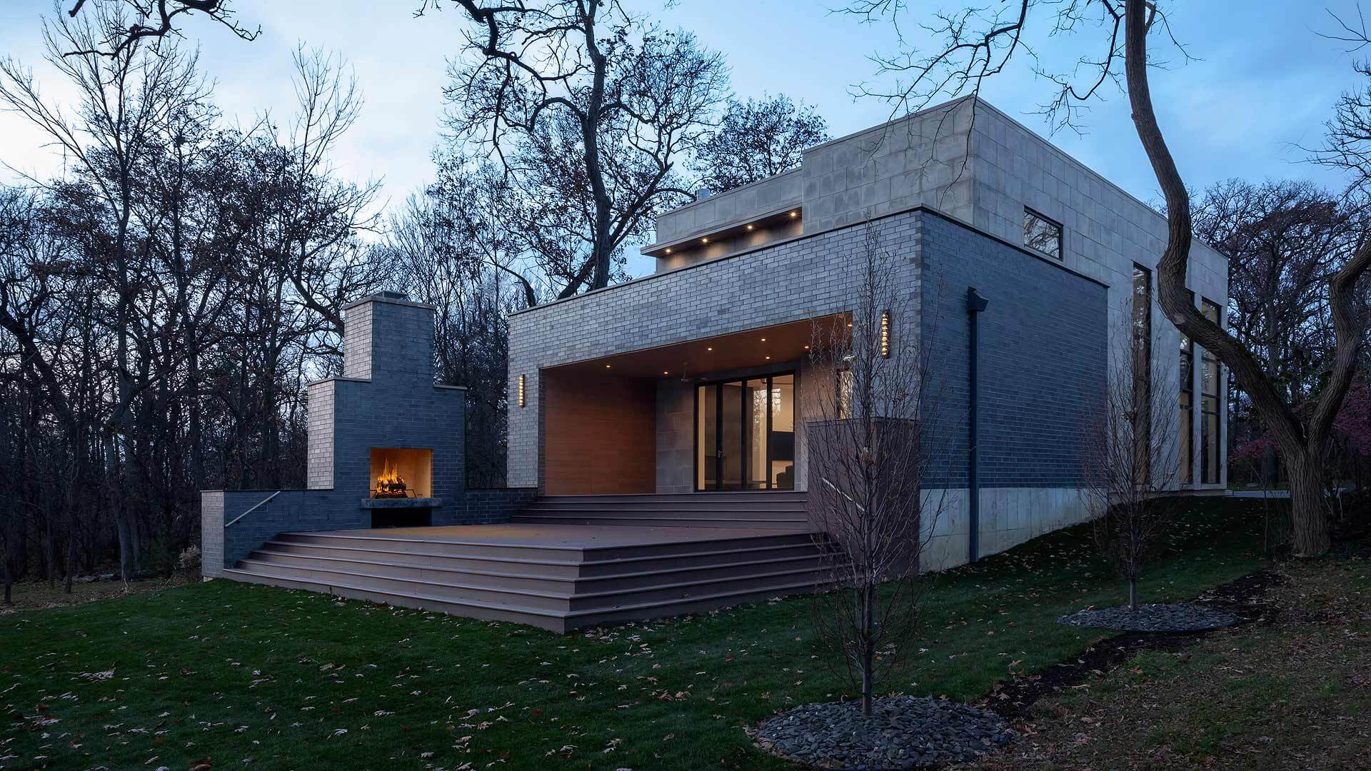 Backyard View shows deck, outdoor fireplace, and covered indoor-outdoor transitional space with Nanwall sliding, bifold exterior glass doors and roof deck - Minimalist Modern - Chicago, Illinois - HAUS | Architecture For Modern Lifestyles, Christopher Short, Indianapolis Architect with Joe Trojanowski