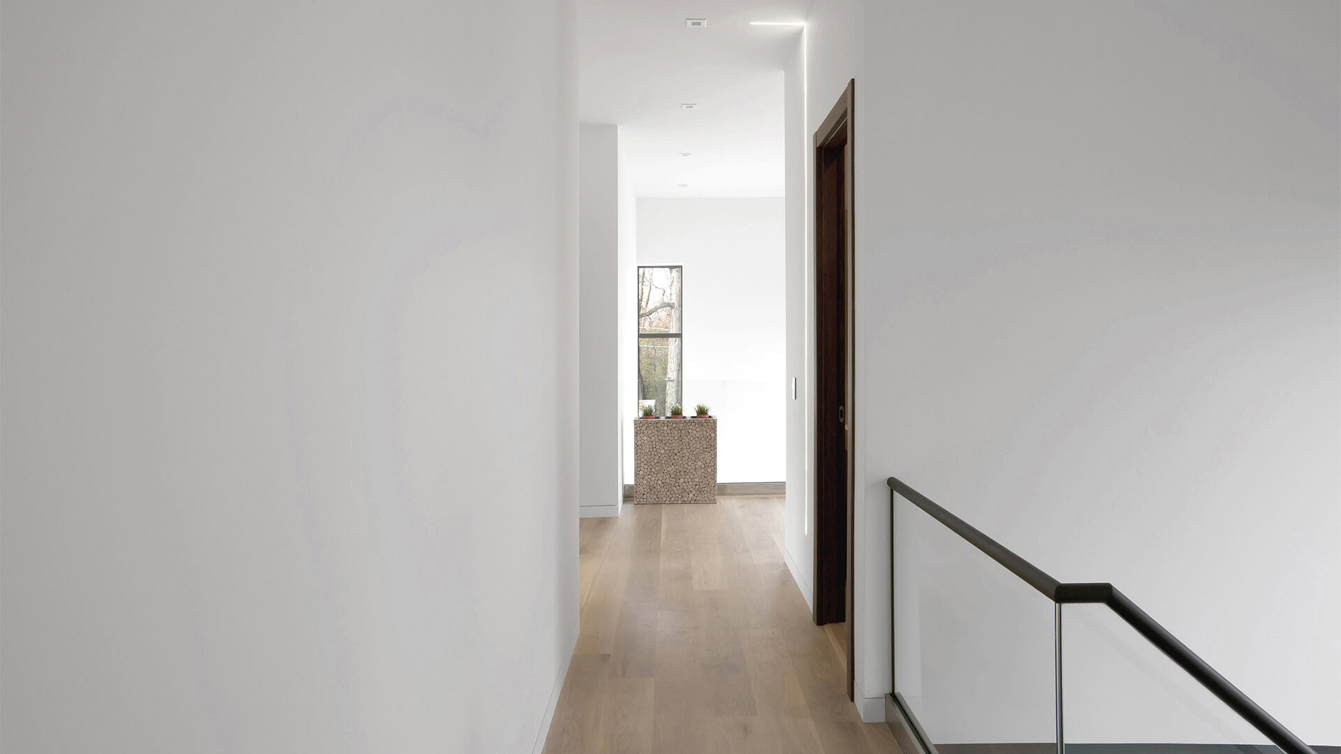 Upstairs Hallway features abundant natural light from stair and two-story entry glazing + LED slot wall/ceiling accent light - Minimalist Modern - Indian Head Park - Chicago, Illinois - HAUS | Architecture For Modern Lifestyles, Christopher Short, Indianapolis Architect with Joe Trojanowski