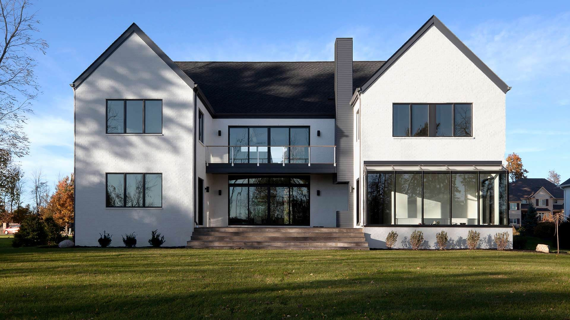 Colonial Modern Complete - Rear exterior elevations features elevated courtyard, cable-rail balcony, grill-station, and sunroom glazing - Towne Oak Estates, Steffe Drive, Carmel, Indiana - Christopher Short, Derek Mills - Indianapolis Architects, HAUS | Architecture For Modern Lifestyles