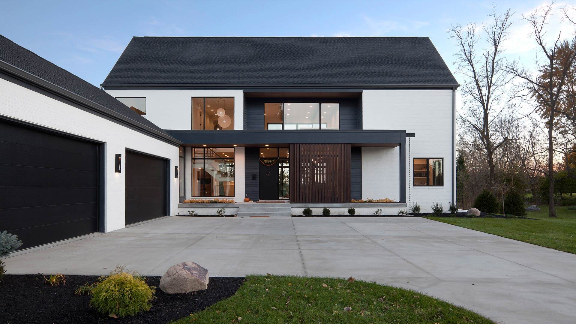 On approach, home presents a simple, semi-formal geometry featuring oversized windows, wood screenwall, with modern flat roof and rainchain detail - Towne Oak Estates, Steffe Drive, Carmel, Indiana - Christopher Short, Derek Mills - Indianapolis Architects, HAUS | Architecture For Modern Lifestyles