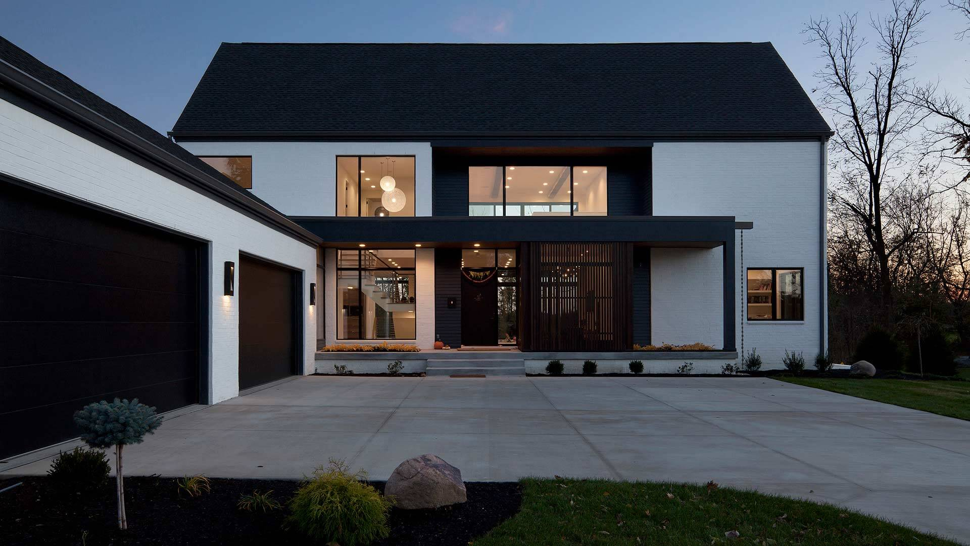 Front twilight exterior elevation features sliding screenwall, flat entry roof, and rainchain - Towne Oak Estates, Steffe Drive, Carmel, Indiana - Christopher Short, Derek Mills - Indianapolis Architects, HAUS | Architecture For Modern Lifestyles