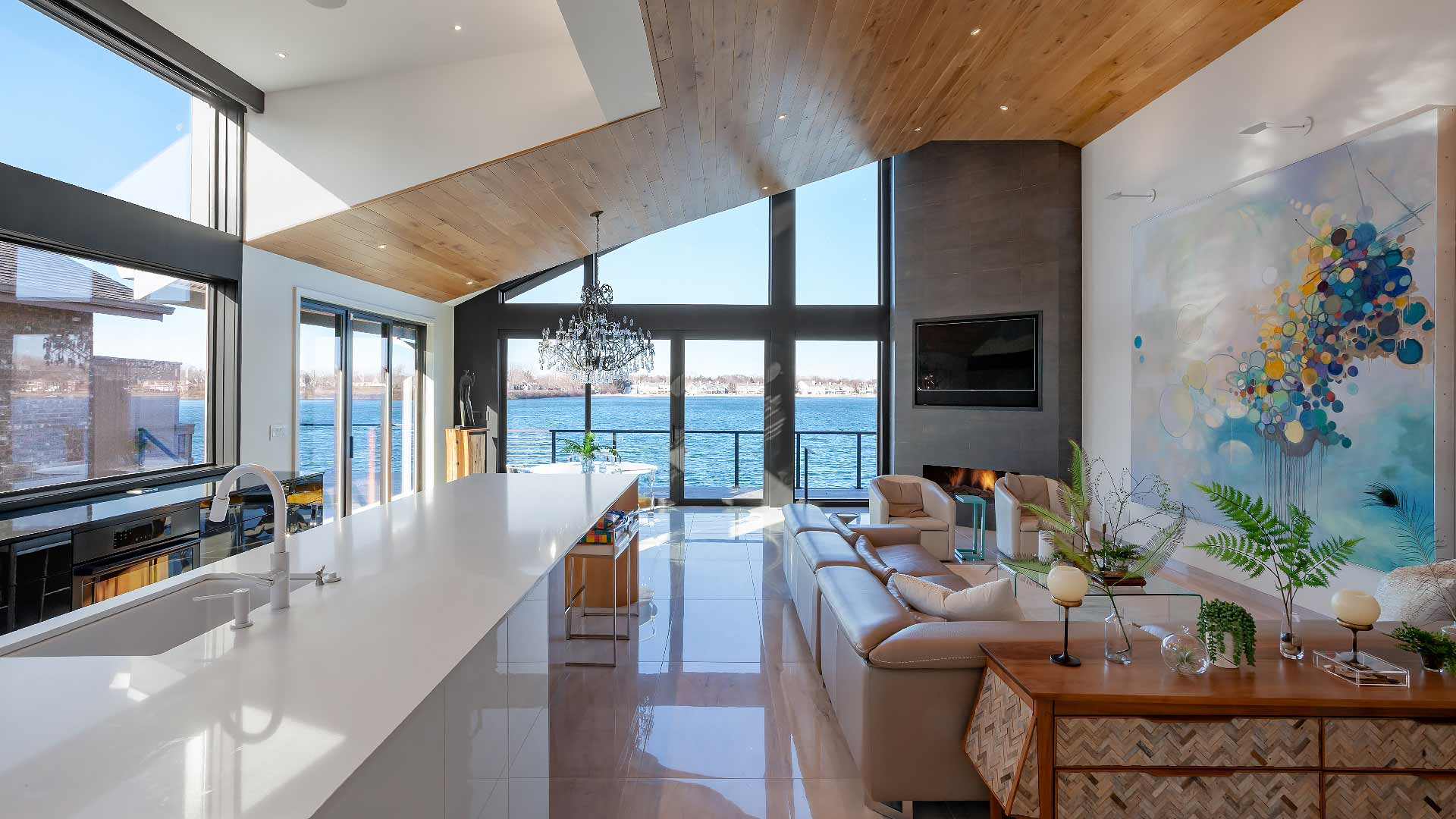 Once you turn the corner upon entry, panoramic lake-side view greets you in the wide-open kitchen, dining, living space - Modern Lakehouse Renovation - Clearwater - HAUS | Architecture For Modern Lifestyles - Christopher Short, Architect - Derek Mills, Project manager - WERK | Building Modern (Construction Manager + Custom Builder)