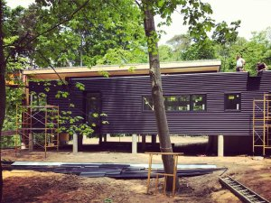 South Exterior Elevation - Extra Dark Bronze Metal Corrugated Siding Progress - Bridge House - Douglas, Michigan - Lake Michigan