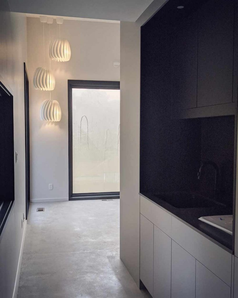 Entry to Art Studio features modern pendant lighting, custom cabinetry, and large windows - Back40House - Pendleton, IN