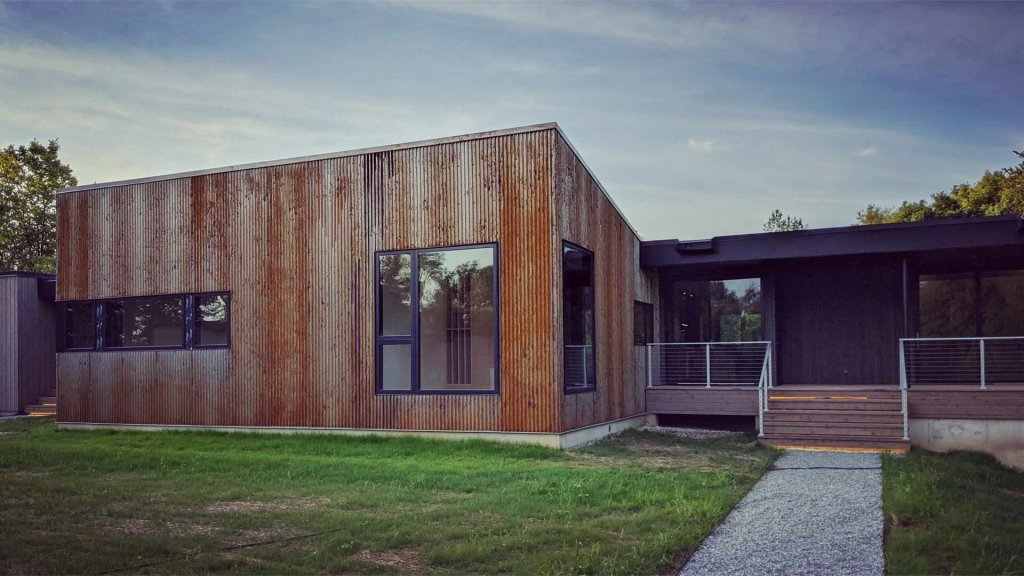 At north exterior elevation, Corten-wrapped studio stands-out next to the adjacent covered porch - cable rail - Cedar decking - flat roof scuppers - Back40House - Pendleton, IN