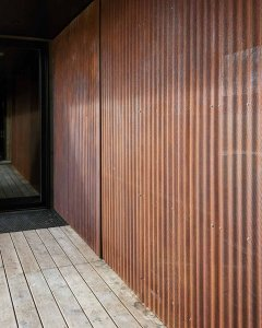 Perforated corrugated Corten cladding shields hot tub area from front entry at breezeway - Back40House - Pendleton, IN