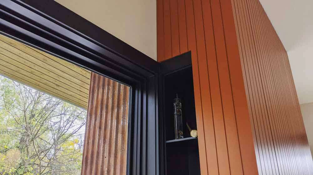 Two sided fireplace balances inside materials and outside materials - Corrugated Corten steel - custom storage niche blends with window frame in side of fireplace enclosure - Back40House - Pendleton, IN