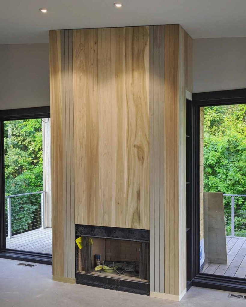 Living Room interior fireplace enclosure continues Corten theme to interior with vertical Poplar and Boral trims - Exterior fireplace enclosure uses corrugated Corten - Back40House - Pendleton, IN