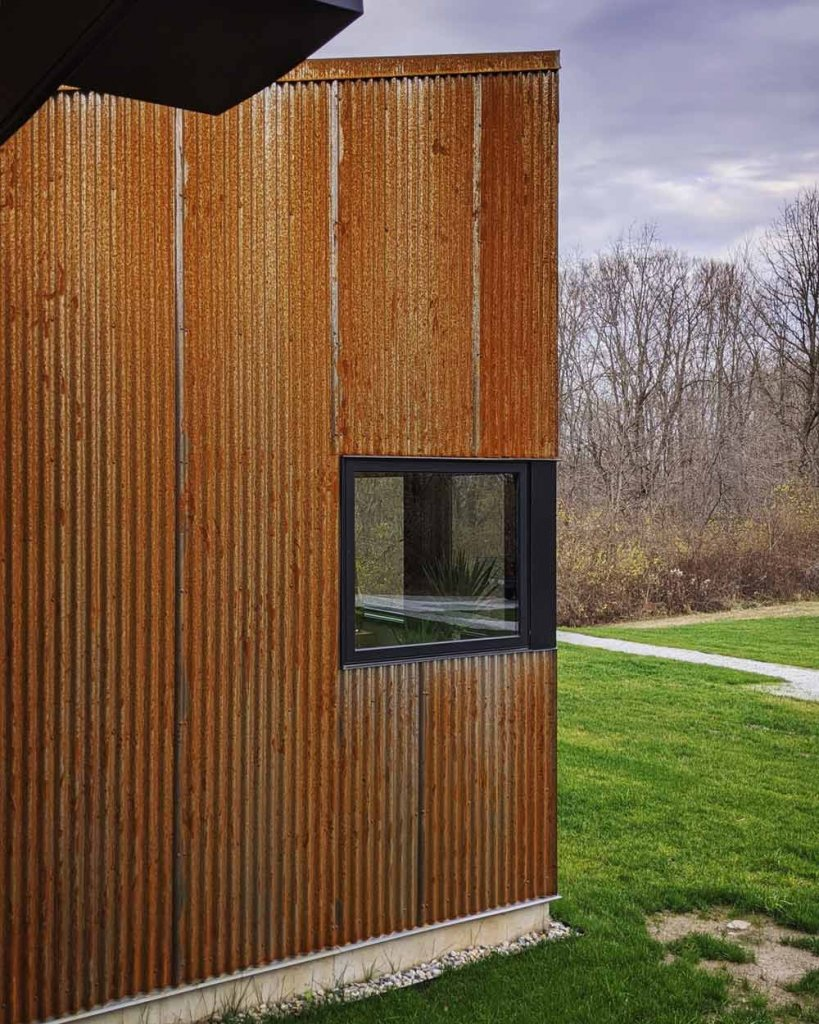 View of Master Suite facade from hot tub enclosure - vertical corrugated Corten steel siding patinas - Back40House - Pendleton, IN
