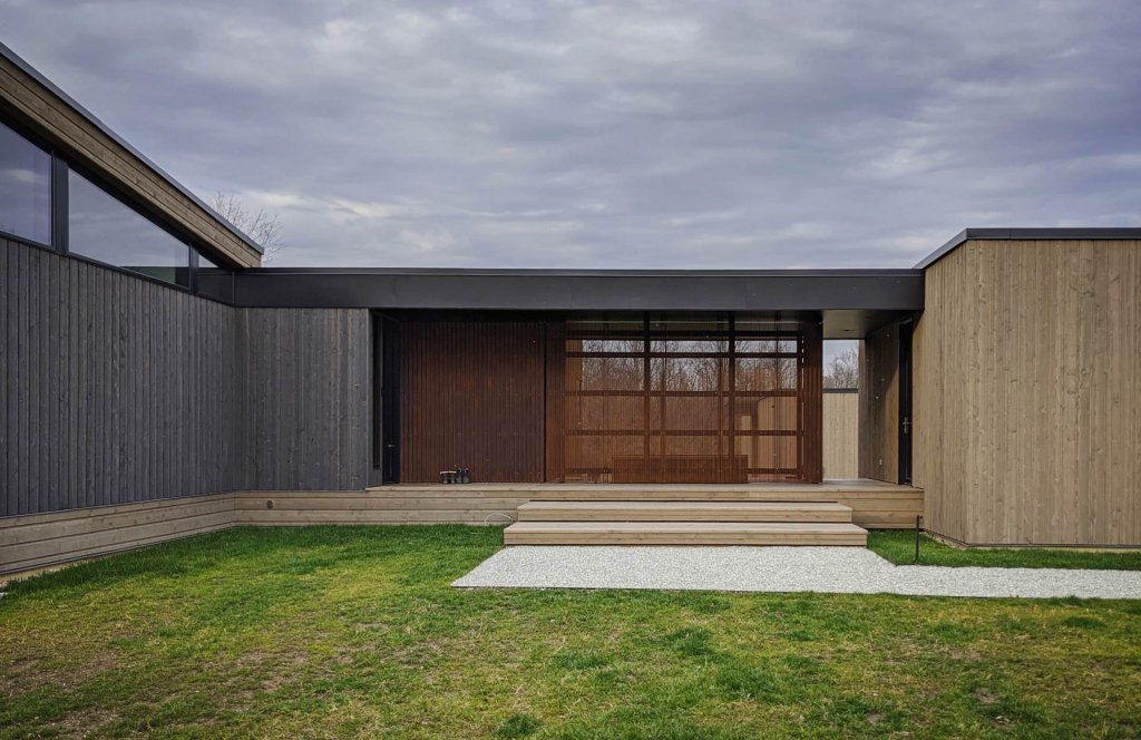 South exterior elevation features two-tone Cedar rustic channel siding and corrugated, perforated Corten steel siding - Back40House - Pendleton, IN