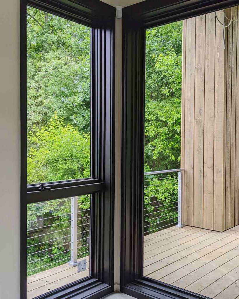 View outside corner window from Living space through west covered porch deck - stainless steel cable railing - Viewrail - black window frames - Back40House - Pendleton, IN